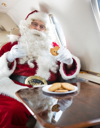 Man in Santa costume eating cookies while holding milk glass in private jet photo