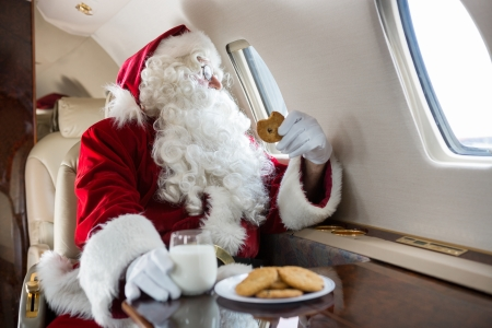 the window: Man in Santa costume holding cookie while looking through private jets window Stock Photo