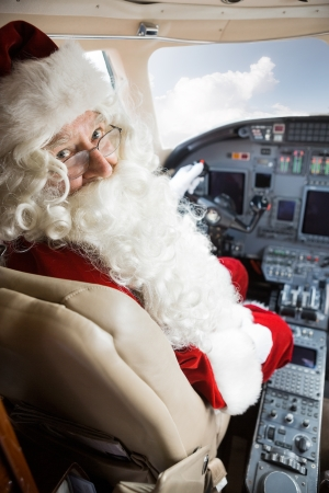 Portrait of man in Santa costume sitting in cockpit of private jet photo