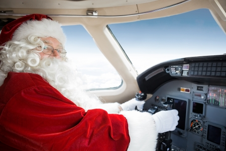 Portrait of man in Santa costume holding control wheel in cockpit of private jet photo