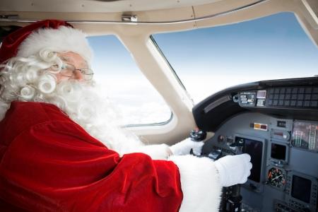 cockpit: Portrait of man in Santa costume holding control wheel in cockpit of private jet