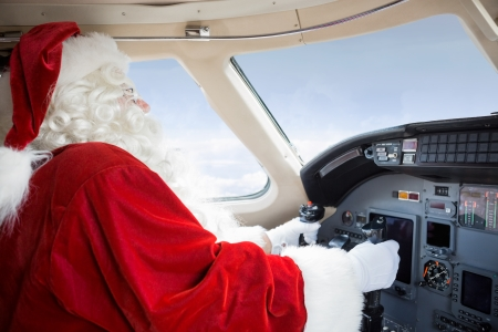Man in Santa costume holding control wheel in cockpit of private jet Stock Photo