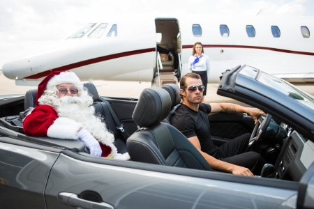 chauffeur: Portrait of Santa and driver in convertible with airhostess standing against private jet