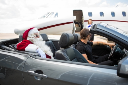 chauffeur: Santa and chauffeur in convertible while airhostess standing against private jet