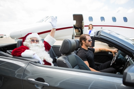 Portrait of Santa waving hand from convertible with private jet in background photo
