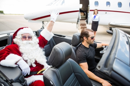 chauffeur: Portrait of Santa waving hand while chauffeur driving convertible with airhostess standing against private jet Stock Photo