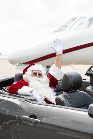 Portrait of Santa waving hand while sitting in convertible against private jet at airport terminal photo