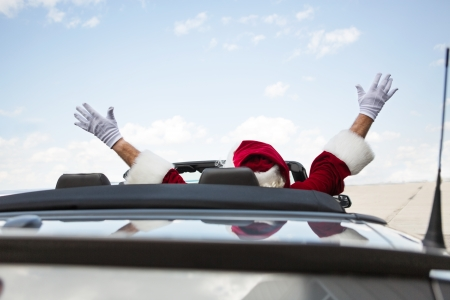 Rear view of Santa with arms raised in convertible