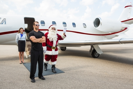 Santa waving hand with bodyguard and airhostess standing against private jet photo