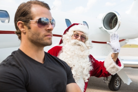 Portrait of Santa waving hand with bodyguard in foreground against private jet at airport terminal photo