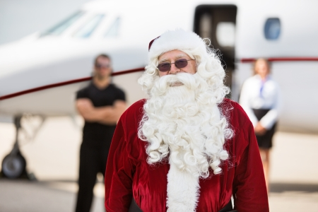 Portrait of man in Santa costume standing against private jet at airport terminal photo