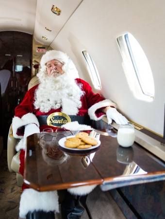 Man in santa costume relaxing on private jet photo