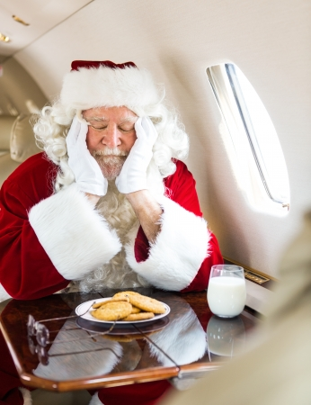 Man in Santa costume with cookies and milk sleeping in private jet photo