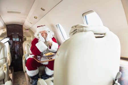 Man in Santa costume with head in hands sleeping in private jet photo