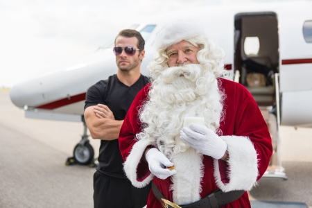 Portrait of Santa holding milk glass while standing with bodyguard against private jet at airport terminal photo