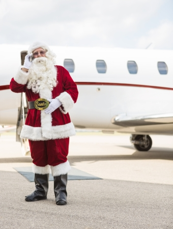 Full length of Santa Claus using cell phone against private jet at airport terminal photo