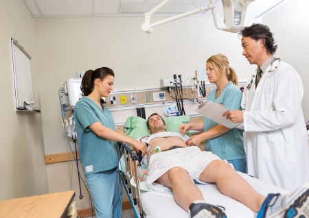 Médico multiétnica y enfermeras que controla al paciente en el hospital Foto de archivo - 23743497