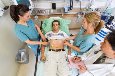 electrocardiograma: Vista de ángulo alto de las enfermeras y del pulso de examen del doctor del paciente en el hospital Foto de archivo