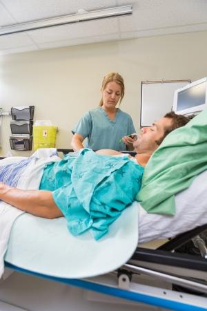 emergency room: Nurse examining male patient in hospital emergency room