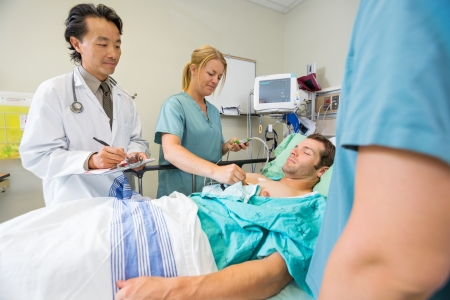 HOSPITAL WARD: Male patient being examined by team of doctors in hospital Stock Photo