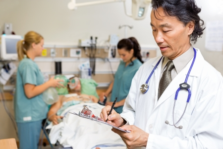 Male doctor writing notes while nurses examine patient in emergency photo
