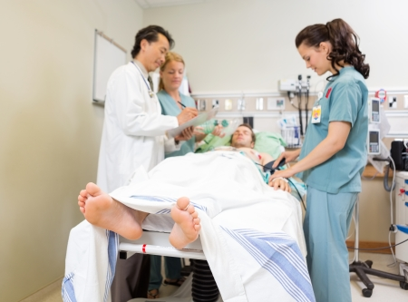 icu: Nurse examining patient while doctor and colleague discussing over report in hospital