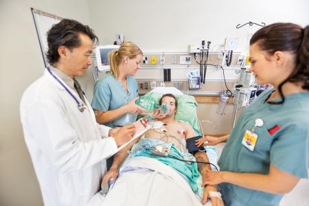Arts die klembord terwijl verpleegkundigen behandelen kritische mannelijke patiënt in het ziekenhuis