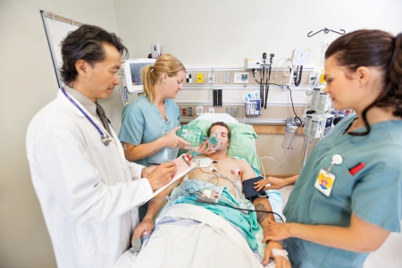 Doctor holding clipboard while nurses treating critical male patient in hospital photo