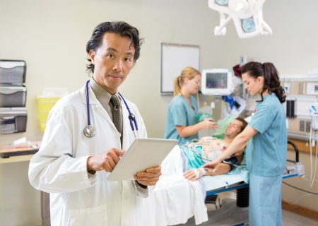 treating: Portrait of male doctor using digital tablet while nurses treating patient in hospital