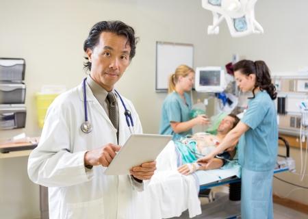 Portret van mannelijke arts met behulp van digitale tablet terwijl verpleegkundigen behandelen patiënt in het ziekenhuis