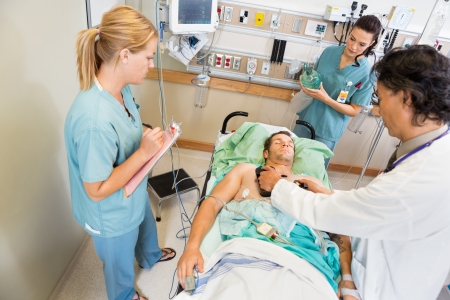 resuscitation department: High angle view of doctor defibrillating critical patient while nurses standing by in hospital Stock Photo