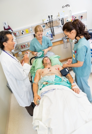 High angle view of nurses and doctor examining critical male patient in hospital photo