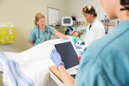 pracoviště: Sestra drží digitální tablet, zatímco lékař a kolega způsobu zpracování zraněný pacient v nemocnici