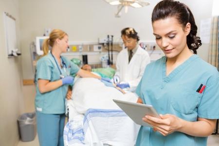 Mooie verpleegster met behulp van digitale tablet terwijl dokter en collega die mannelijke patiënt in het ziekenhuis Stockfoto