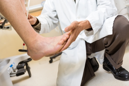 Low section of doctor testing achilles heel of patient photo