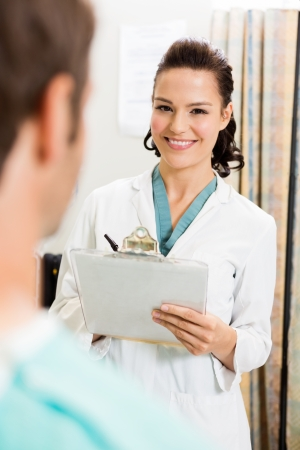 Portrait of beautiful doctor with clipboard standing by patient in hospital photo