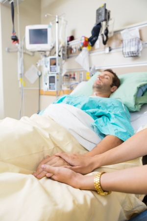 Cropped image of woman holding mans hand lying on bed in hospital