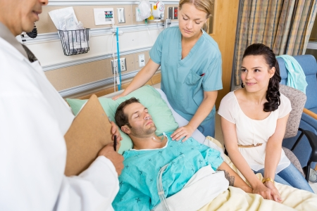 Young woman looking at doctor while holding man's hand in hospital room photo