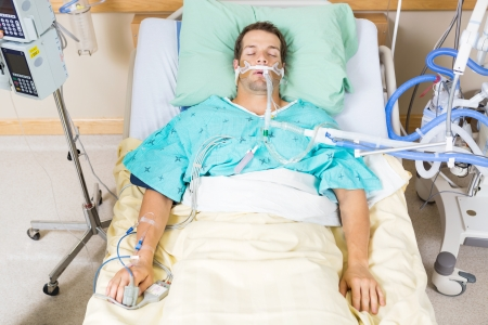 critical care: High angle view of critical patient with endotracheal tube resting on bed in hospital