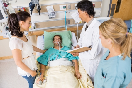 critical care: High angle view of doctor and nurse with woman looking at critical patient in hospital