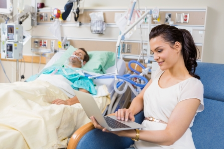 Young woman using laptop while sitting by patient resting in bed at hospital photo