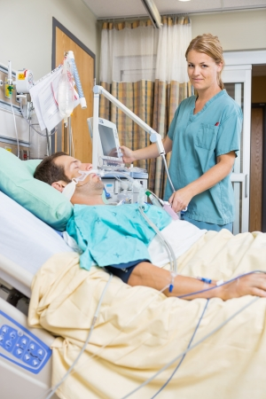 Portrait of nurse examining young patient lying on bed in hospital