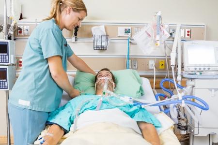 Mid volwassen verpleegkundige aanpassen kussen mannelijke patiënt in het ziekenhuis kamer Stockfoto