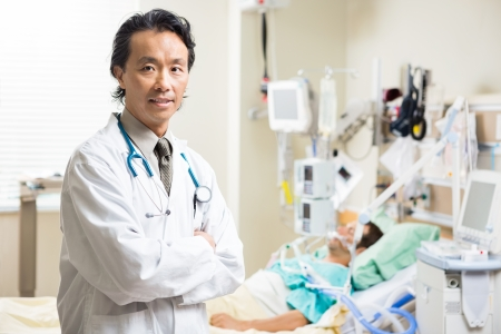 units: Portrait of confident doctor standing arms crossed with patient resting in background at hospital