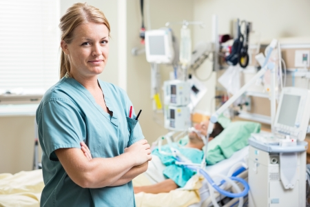 Portrait of confident nurse standing arms crossed with patient resting in background at hospital
