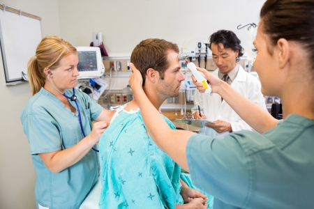 check room: Multiethnic medical team examining male patient in hospital Stock Photo