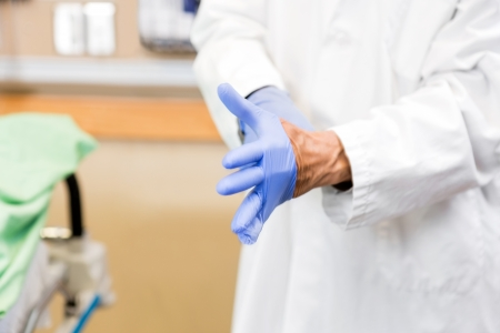sterilized: Midsection of mid adult doctor wearing sterilized gloves in hospital
