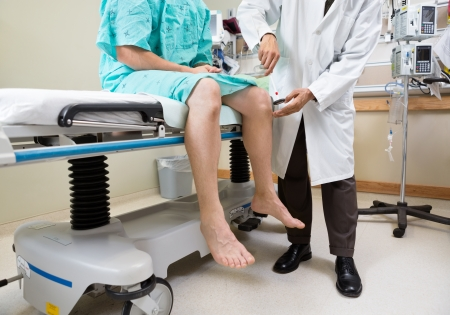 reflex: Low section of neurologist examining patients knee with hammer in hospital room