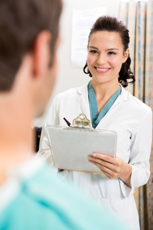 Happy female doctor with clipboard looking at patient in hospital photo