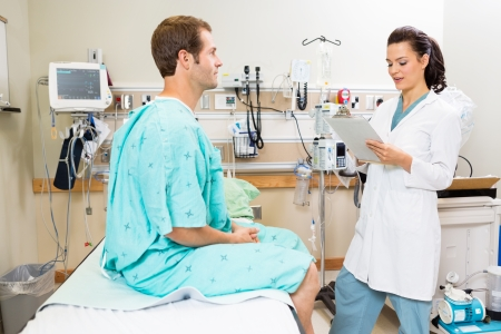 Beautiful doctor with clipboard discussing medical report with male patient in hospital photo